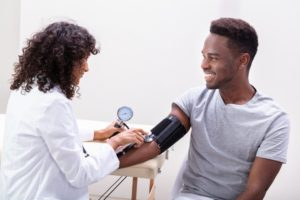 doctor checking a patients' blood pressure