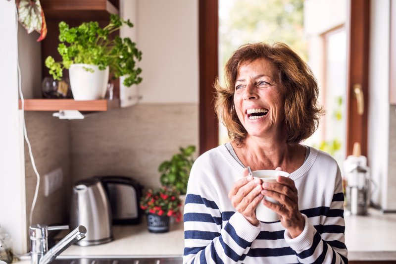 Senior woman smiling while drinking coffee in kitchen