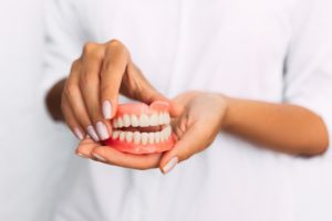 Woman holding ill-fitting dentures